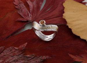 Geschwungener Eisschlagring mit Mandaringranat seitlich Gold und Silber
